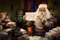 Santa Claus montrant un dessin d'enfant Photographie stock libre de droits