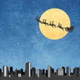 Santa Claus  And Moon recycled papercraft. Santa Claus On Sledge With Deer And Moon above city panorama silhouettes recycled papercraft Royalty Free Stock Photo