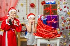 Santa Claus mostró al ayudante del reloj, toda la sonrisa de la diversión Imagen de archivo libre de regalías
