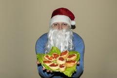 Santa Claus mostra muitos sanduíches com caviar vermelho imagens de stock