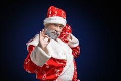 Santa Claus mostra o sinal APROVADO em um fundo escuro fotografia de stock