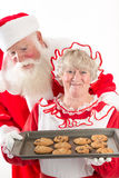 Santa claus and Mrs Santa with cookies. Mrs Claus beams while holding a tray of cookies on a tray, fresh from the oven. Santa looks excitedly over her shoulder royalty free stock image