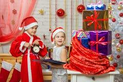 Santa Claus muestra que los ayudantes hora de entregar los regalos de la Navidad Imagen de archivo libre de regalías
