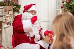 Santa Claus mystérieuse étendant des présents sous l'arbre de Noël photos libres de droits