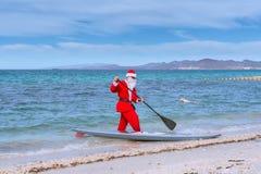 Santa Claus når kusten av stranden med hans bräde arkivfoton