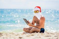 Santa Claus na praia com uma tabuleta nas mãos Fotos de Stock