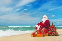 Santa Claus na praia do mar com muitos presentes e Natal decorado Fotografia de Stock Royalty Free