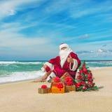 Santa Claus na praia do mar com muitos presentes e Natal decorado Fotos de Stock Royalty Free