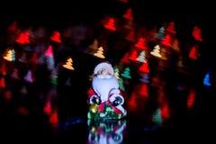 Santa Claus nahe der Geschenkbox auf dem Hintergrund des bunten bokeh in Form von Weihnachtsbäumen Lizenzfreie Stockfotos