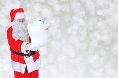 Santa Claus with Naughty and Nice List Silver Bokeh Background stock photography