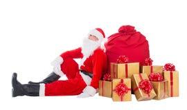 Santa Claus near big red Christmas sack full of gift boxes Royalty Free Stock Photo