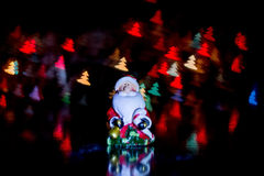 Santa Claus near the gift box on the background of colorful bokeh in the form of Christmas trees Royalty Free Stock Photos