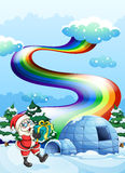 Santa Claus near the igloo and a rainbow in the sky Stock Image