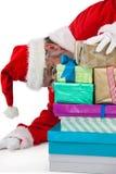 Santa Claus nederlag bak gåvorna Fotografering för Bildbyråer