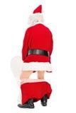 Santa Claus-nemen piss in een toilet Stock Foto's