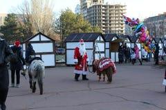 Santa Claus an neues Jahr ` s Tag bietet an, sich auf Kinder zu stürzen Es ist auf dem Quadrat, auf dem es viele Leute und Shops  Stockfotos