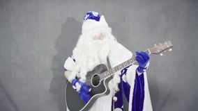 Santa Claus no terno azul joga a guitarra video estoque
