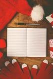 Santa Claus notebook for good children wish list. Santa Claus work desk, empty notebook as copy space for good children wish list, hat and gloves with Christmas Royalty Free Stock Photos