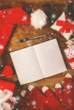 Santa Claus notebook for good children wish list. Santa Claus work desk, empty notebook as copy space for good children wish list, hat and gloves with Christmas Royalty Free Stock Images