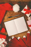 Santa Claus notebook for good children wish list. Santa Claus work desk, empty notebook as copy space for good children wish list, hat and gloves with Christmas Stock Image