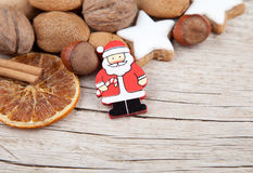 Santa Claus with nuts, oranges and cookies at the edge of wood Royalty Free Stock Photos