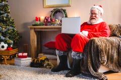 Santa Claus obsiadanie i używać w domu laptop Zdjęcia Royalty Free