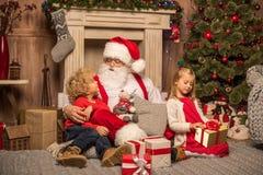 Santa Claus och barn med julgåvor Royaltyfria Foton