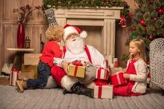 Santa Claus och barn med julgåvor Royaltyfri Bild