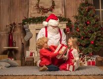 Santa Claus och barn med julgåvor Arkivbild