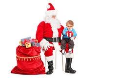 Santa Claus och barn med posera för gåva Fotografering för Bildbyråer
