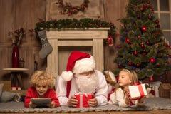 Santa Claus och barn som ligger på matta Arkivfoto