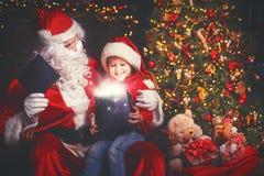Santa Claus och barnflicka med den ljusa magiska gåvan i jul Royaltyfri Foto