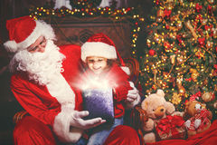 Santa Claus och barnflicka med den ljusa magiska gåvan i jul Arkivbilder