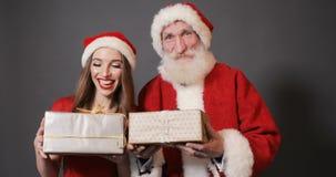 Santa Claus och den kvinnliga hjälpredan ger gåvor lager videofilmer