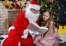 Santa Claus och en flicka i en klänning Julplatser Fotografering för Bildbyråer