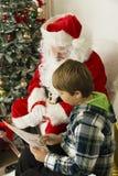 Santa Claus och en pojke som ser papper Arkivfoto