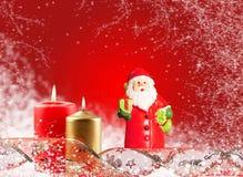Santa Claus och en stearinljus på en röd bakgrund Royaltyfria Foton