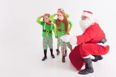 Santa Claus och för ungar iklädda Elven dräkter is little norr pingvinpol för natt Fotografering för Bildbyråer