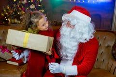 Santa Claus och flicka med julgåvor Fotografering för Bildbyråer