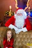 Santa Claus och flicka med julgåvor Arkivbild