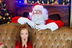 Santa Claus och flicka med julgåvor Royaltyfria Bilder