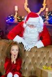 Santa Claus och flicka med julgåvor Royaltyfri Foto