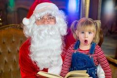 Santa Claus och flickor som läser en bok Fotografering för Bildbyråer