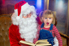 Santa Claus och flickor som läser en bok Arkivbilder