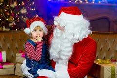 Santa Claus och flickor som läser en bok Royaltyfri Bild