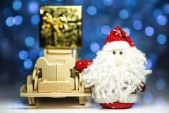 Santa Claus och gammal retro träbil med gåvaasken Royaltyfri Fotografi