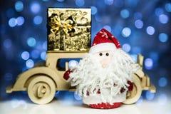 Santa Claus och gammal retro träbil med gåvaasken Arkivfoton