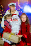 Santa Claus och grupp av flickor med julgåvor Arkivfoto