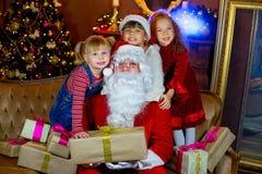 Santa Claus och grupp av flickor med julgåvor Royaltyfri Bild