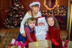 Santa Claus och grupp av flickor med julgåvor Arkivbilder